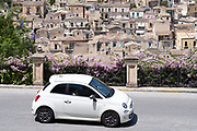 White colour Fiat 500 Cinquecento in hill city of Modica Alta looking towards Modica Bassa, Sicily, Italy