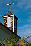 A bird lands on the broken cross on top of a church steeple in Hawaii.