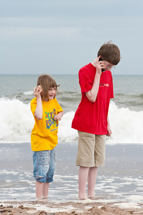 """Children on a beach with cell phone and """"shell phone"""", Scotland"""