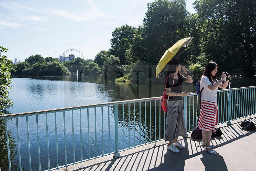 © Licensed to London News Pictures. 23/07/2018. London, UK. Tourists shelter underneath an umbrella from the early morning sun in St James's Park central London, as the hot weather continues in the capital. Forecasters are predicting record temperatures this week. Photo credit: Ben Cawthra/LNP