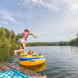 A girl jumps into Island Pond at Red River Camps in Aroostook County, Maine. Deboullie Public Reserve Land.