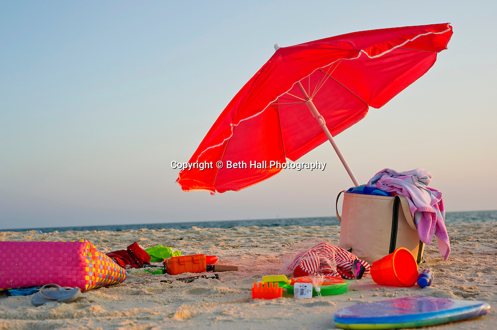 A single red umbrella sits on the beach surrounded by toys as the sun sets.
