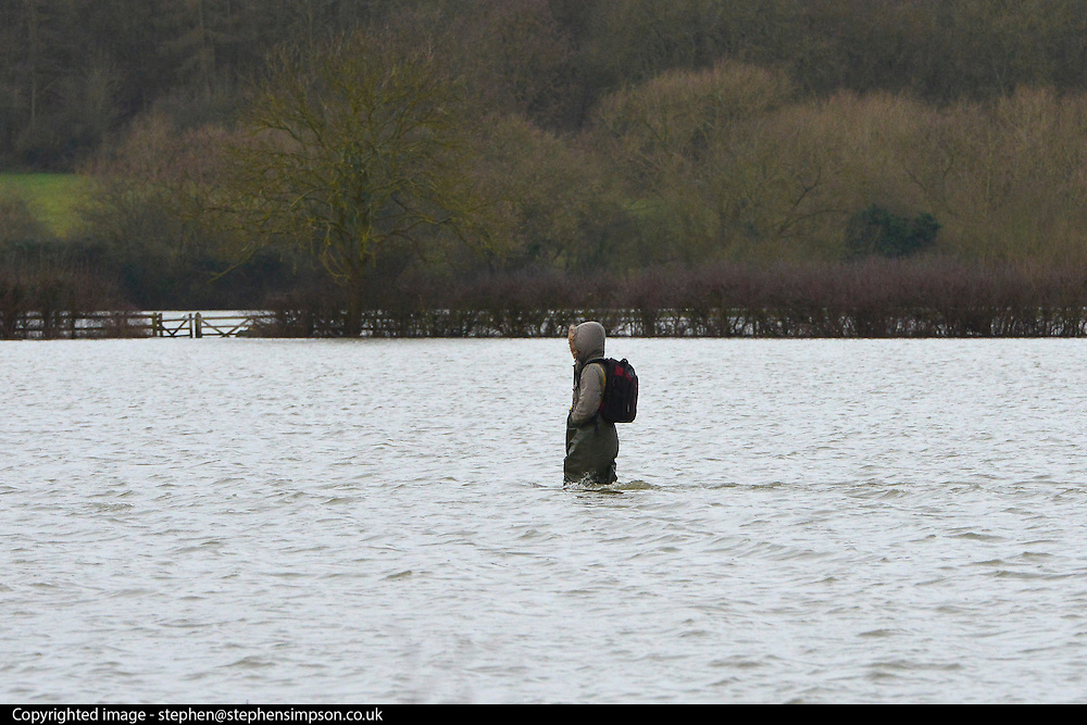 © Licensed to London News Pictures. 12/02/2014. Old Windsor, UK. A man walks across a flooded field.  Flooding in OLD WINDSOR in Surrey today 11th February 2014 after the River Thames burst its banks. The Environment Agency has issued 14 Severe Flood Warnings alone the Thames. Photo credit : Stephen Simpson/LNP