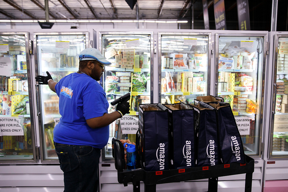 Ryan White, Amazon associate, looks for items from a freezer while filling shopping bags with products for customers orders at the Amazon.com Inc. Prime Now fulfillment center warehouse on Monday, March 27, 2017 in Los Angeles, Calif. The warehouse can fulfill one and two hour delivery to customers. Complex supply chains such as Amazon's and e-commerce trends will impact city infrastructure and how things move through cities. © 2017 Patrick T. Fallon