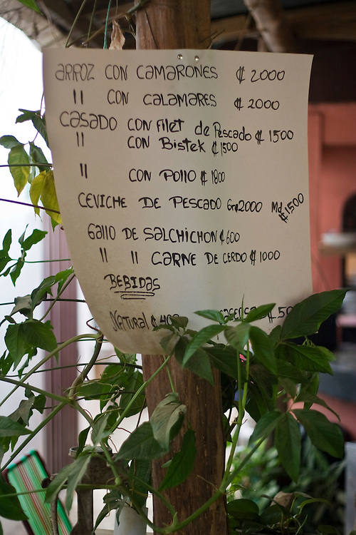 a menu in Spanish is displayed outside a local restaurant in Guanacaste, Costa Rica.