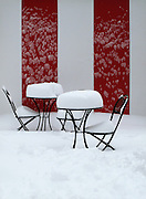 A very thick blanket of show is covering cafe tables and chairs outside a red and white tent in Central Park in New York City.