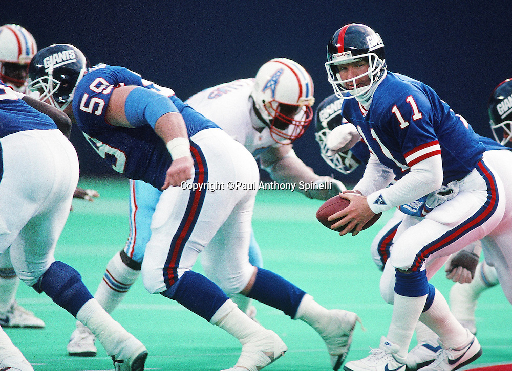 New York Giants quarterback Phil Simms (11) takes a snap during the NFL football game against the Houston Oilers on Dec. 21, 1991 in East Rutherford, N.J. The Giants won the game 24-20. (©Paul Anthony Spinelli)