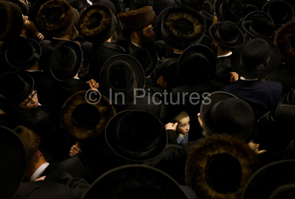 A young Orthodox Jewish boy surrounded by hundreds of Orthodox Jewish men wearing black coats and hats. The men are gathered to see their spiritual leader who has arrived from Antwerp.