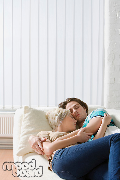 Young couple embracing napping on sofa