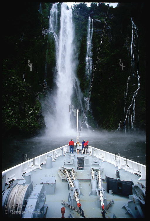 Cruise ship Clipper Odyssey noses bow to base of 530'-high Stirling Falls in Milford Sound; Fiordland Natl Park, New Zealand.