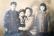 deteriorating family group studio portrait Japan ca 1940s 1950s