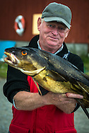 Namsos, Namdal, Trondelag, Norway, July 2015. A Fisherman shows his catch of the day on the camping of Aglen on the Otteroya peninsula. Trøndelag lies at the heart of Norway's identity. The rolling hills of the interior with its traditional ox-blood coloured farm houses grow a wealth of produce. In the west the coastline is sculpted by a maze of fjords and islands home to small fishing communities. Photo by Frits Meyst / MeystPhoto.com