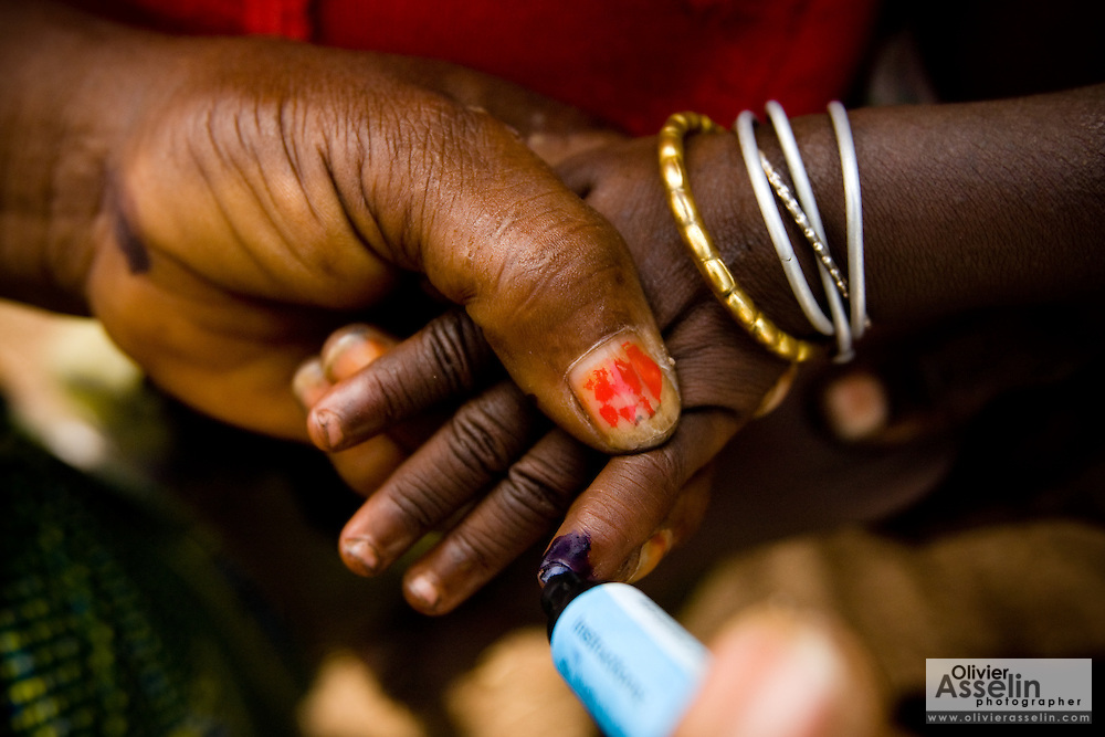 A community volunteer marks the finger of a child with ink during a national polio immunization exercise in the village of Gidan-Turu, northern Ghana on Thursday March 26, 2009.