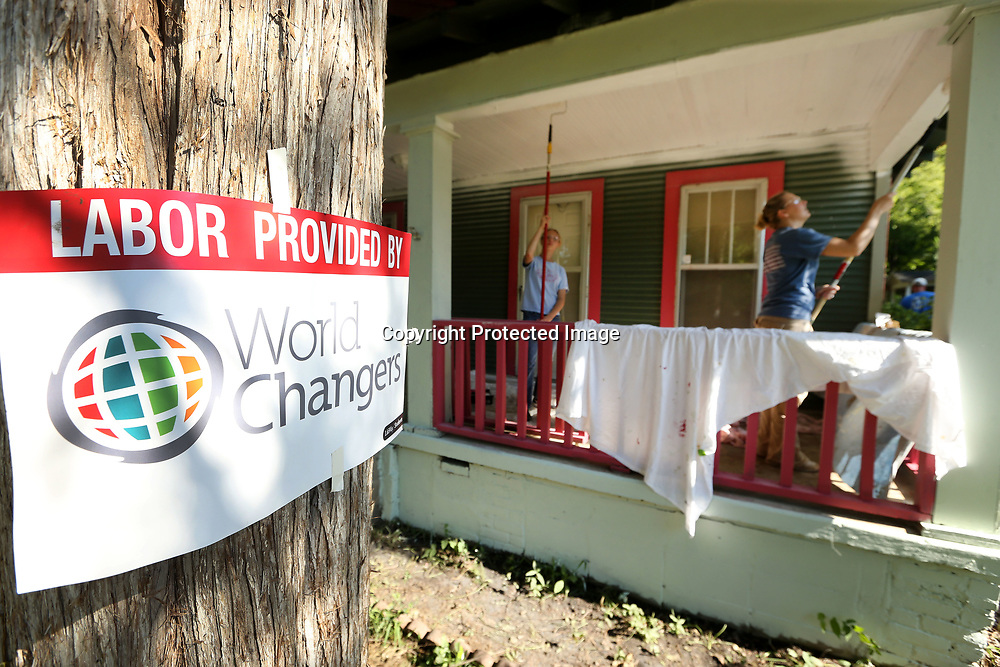 World Changers paint the home of Tupelo resident Robi Gutierrez on Chestnut Street in Tupelo Wednesday. The group will be working on several different homes in the area until Friday.