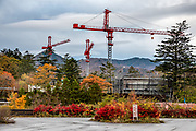 RestauConstruction cranes in October 2018 in Chuzenjiko Onsen, Nikko, Tochigi Prefecture, Japan. Lake Chuzenji (Chuzenjiko) is a scenic lake in the mountains above the town of Nikko. It's at the foot of Mount Nantai, Nikko's sacred volcano, whose eruption blocked the valley below, thereby creating Lake Chuzenji 20,000 years ago. Chuzenjiko's shores are mostly undeveloped and forested except at the eastern end where the growing hot spring town of Chuzenjiko Onsen was built. Chuzenjiko is especially beautiful in mid to late October, when the autumn colors reach their peak along the lake's shores and surrounding mountains. See panoramic views of Lake Chuzenji along the Chuzenjiko Skyline, an eight kilometer long former toll road accessible by bus or car, which also connects to scenic hiking trails.