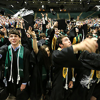 Members of the Mooreville High School graduating class of 2019 celebrate as they toss their caps in the air at the end of their graduation ceremony at the BancorpSouth Arena on Saturday.