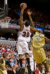 Georgia Tech forward/center Alade Aminu (44) fouls Virginia forward Adrian Joseph (30) on a shot.  The Virginia Cavaliers men's basketball team fell to the Georgia Tech Yellow Jackets 92-82 in overtime at the John Paul Jones Arena in Charlottesville, VA on January 27, 2008.
