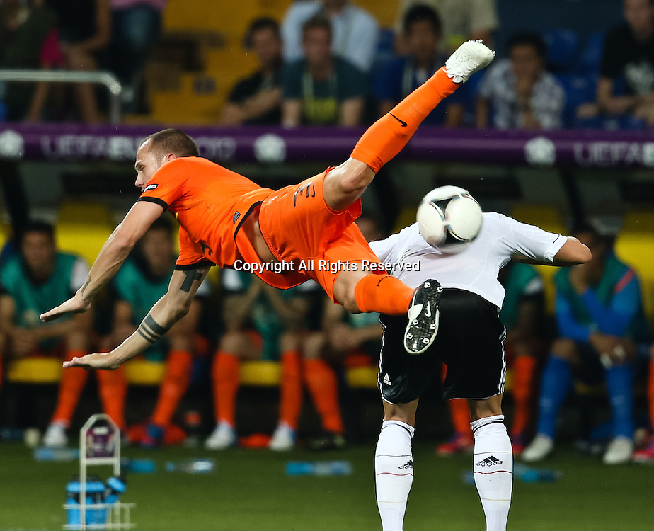 13.06.2012 Ukraine, Kharkiv.  Netherlands national team player John Heitinga] (left) and German national team player in the group stage European Football Championship match between teams of the Netherlands and Germany.