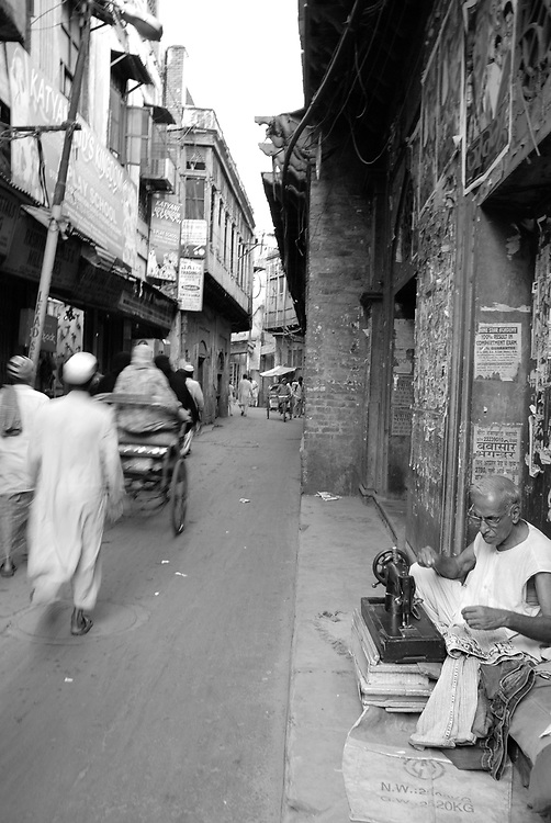 A tailor works in a narrow alleyway of Old Delhi, India