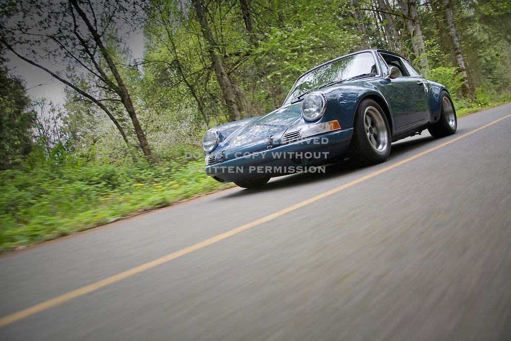 Image of a blue sports car driven fast on country road,  Porsche 911 ST in Seattle, Washington, Pacific Northwest, property released
