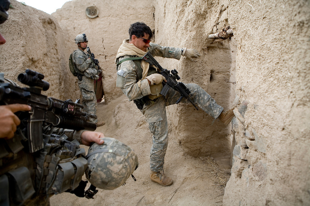 Sargeant Nathan Robertson of the 82nd Airborne kicks down a door while searching for Taliban in the village Kshahah Lakhchack, Kandahar province, Afghanistan on Monday, March 26, 2007.