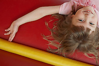 Girl (5-6) lying down in bouncy castle portrait close up view from above