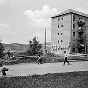 Children play in a housing estate surrounded by communist style housing blocks in the heart of a housing estate in the small Romanian town of Copsa Mica,  Transylvania, Romania. Copsa Mica was once described as the most polluted town in Europe. May 9, 2008. Photo Tim Clayton....Copsa Mica, a small industrial town deep in Transylvania, Romania, was described during the 1990s as the most polluted town in Europe with lead levels reaching were more than 1000 times the allowable International limits and life expectancy nine years shorter than the National average...The pollution was caused entirely by two factories, Carbosin produced black for dies and tires and closed in 1993 while Sometra, a nonferrous smelter is still operational today...The pollution was so bad sheep were black, covered in soot and health officials advised against eating livestock or vegetables and drinking the water or milk...The Communist rule of Nicolae Ceausescu is blamed for the widespread environmental degradation that left industrial parts of Romania in ecological disaster. Industry was situated in a way to concentrate pollution in small areas leaving the rest of the country relatively free of pollution. Copsa Mica in particular was left an environmental disaster...The pollution caused a direct affect on human health with widespread Lung disease, Impotency, the highest infant mortality rate in Europe, Lead poisoning and behavioral problems...Fifteen years on since the closure of Carbosin in 1993, the factory skeleton remains as part of the towns bleak landscape, Unfinished communist style housing blocks still stand in the heart of the towns housing estate. The town's inhabitants are still trying to recover from the long lasting effects of pollution...Recent survey's found the soil contained so much lead that it was 92 times above the permitted level; the vegetation had a lead content 22 times above the permitted level. While toxins have penetrated at least one meter (three fe