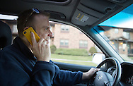Nick Rhoades talks on the phone with a coworker as he drives to the store in Waterloo, Iowa on Thursday, November 7, 2013.