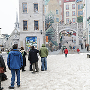 A massive mural on the side of a building in Quebec City's Old Town depicts and idyllic Quebecois life. Tourists stand on the snow-covered ground looking at the mural.