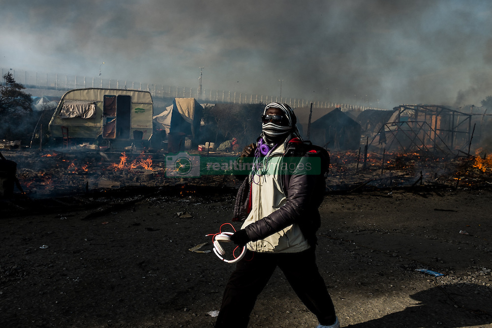 October 26, 2016 - Calais, France - A migrant walks between burned down huts in the Calais Jungle, on October 26, 2016. Huge fires destroyed a mayor part of the refugee camp today. (Credit Image: © Markus Heine/NurPhoto via ZUMA Press)