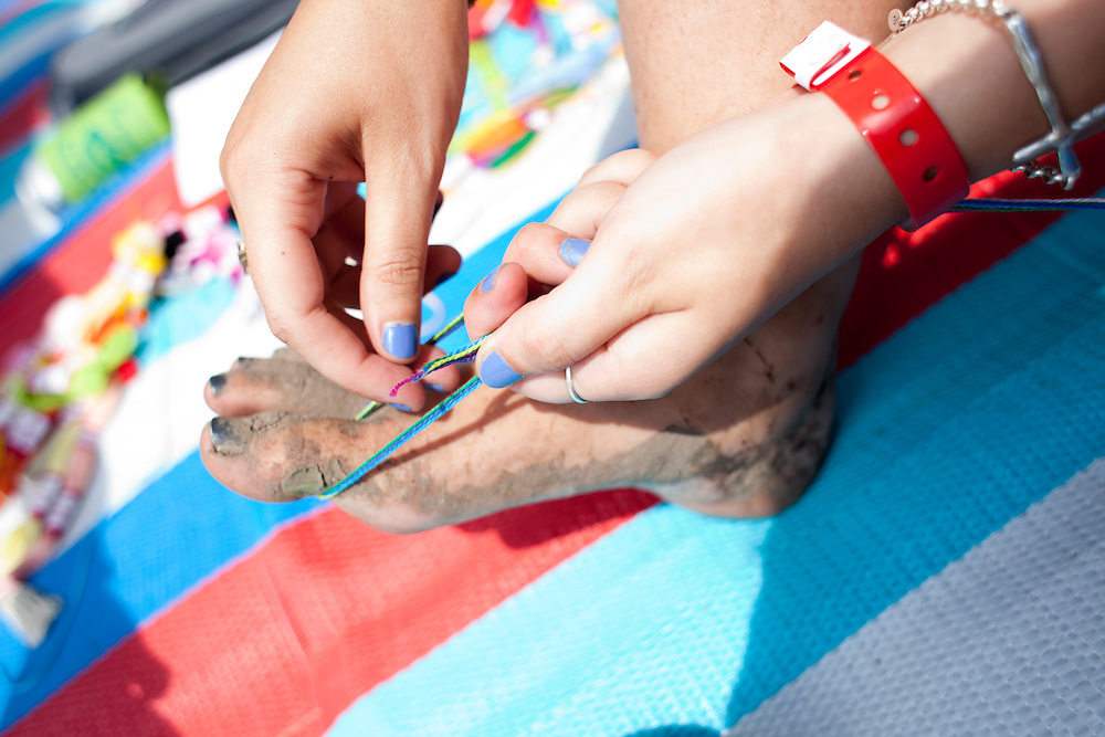 Emily Carter of Beaverdale braids a friendship bracelet at Camp Euforia north of Lone Tree on Friday, July 18, 2015. The music festival gathers over a thousand campers and visitors to Jerry Hotz's 120-acre farm every year.
