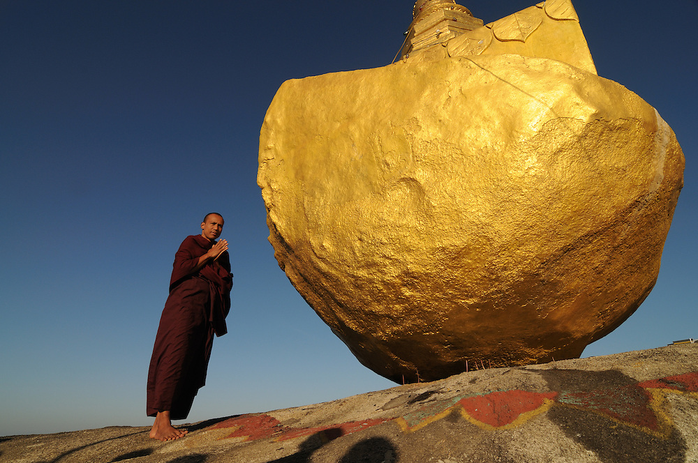 Monk praying before the golden rock, Kytiku, Myanmar, Asia