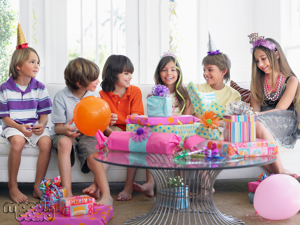 Group of children (7-12) sitting on sofa at birthday party