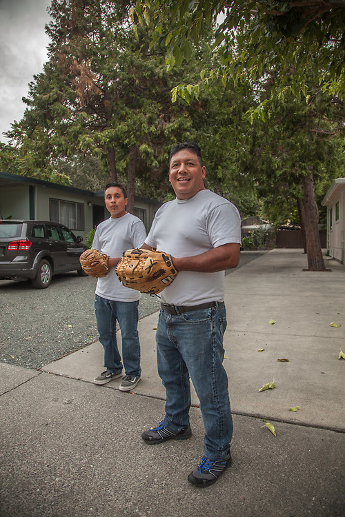 """Manuel Rodriguez and his 13 yeare old son, Adan, play catch in the driveway just minutes before the start of Game One of the World Series.  """"We are rooting for Kansas City...this is their year...they deserve it.""""  rodriguez.adan29@yahoo.com"""