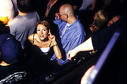 A female clubber lending her ear to a friend on another level trying to tell her something, UK 2000's
