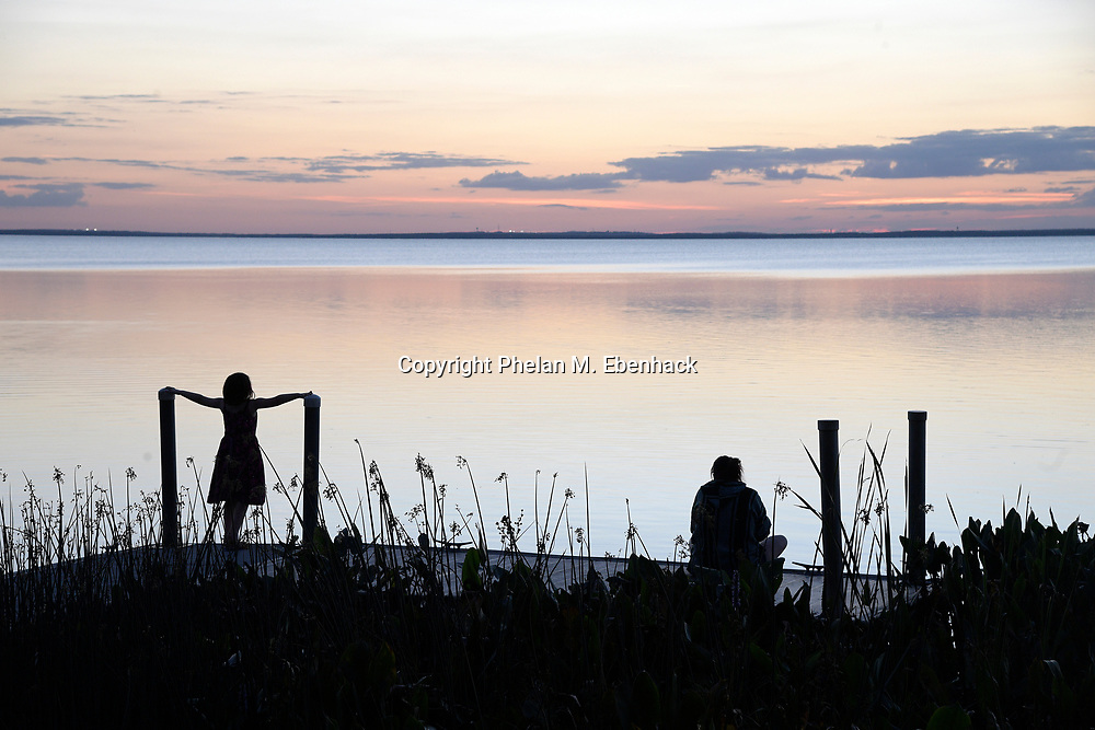 Visitors watch a sunset over Lake Apopka from a boat dock at Magnolia Park, Monday, Jan. 16, 2017, in Apopka, Fla. (Photo by Phelan M. Ebenhack)