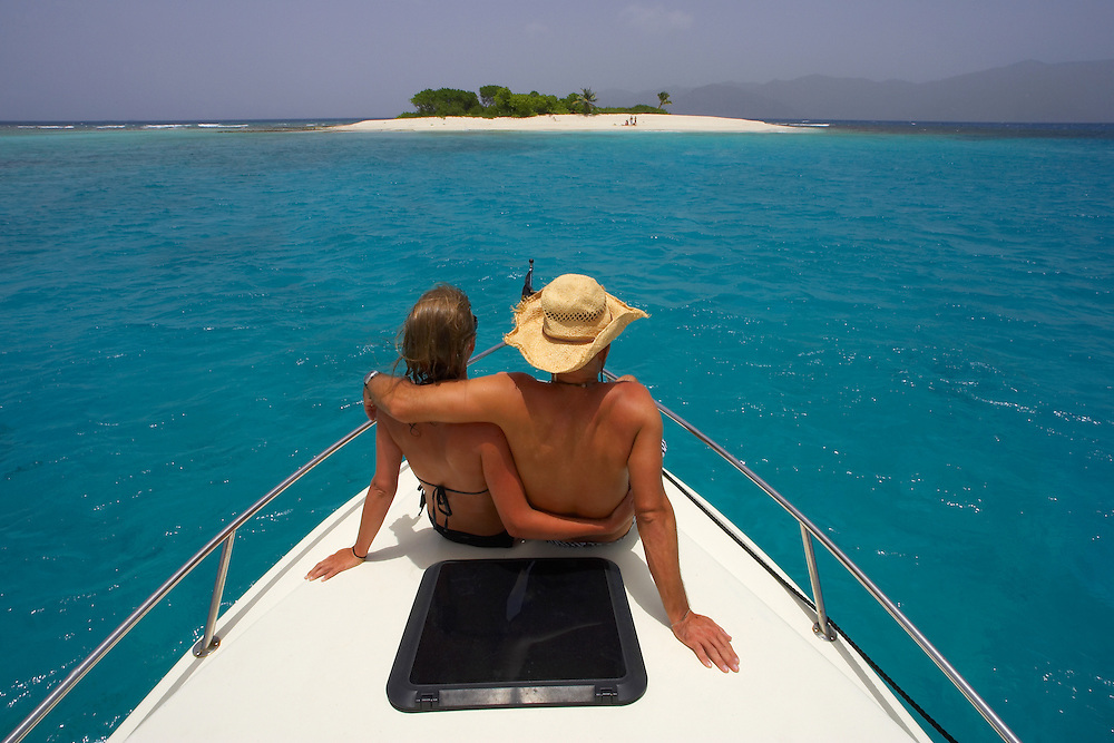 Travel. A couple relax on the deck of a boat anchored at Sandy Spit in the British Virgin Islands