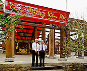 Founders (and funders) of a new pagoda in Battrang town in North Vietnam stand proudly in front of the half finished structure.  They wear white shirts and neckties with black trousers.  They seem to represent the increasing wealth of the local pottery making region, which ships throughout Asia.