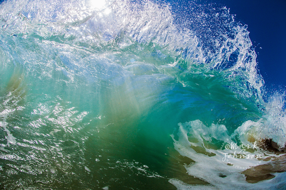 Backlit breaking wave with frilly lip and water drops, Hawaii