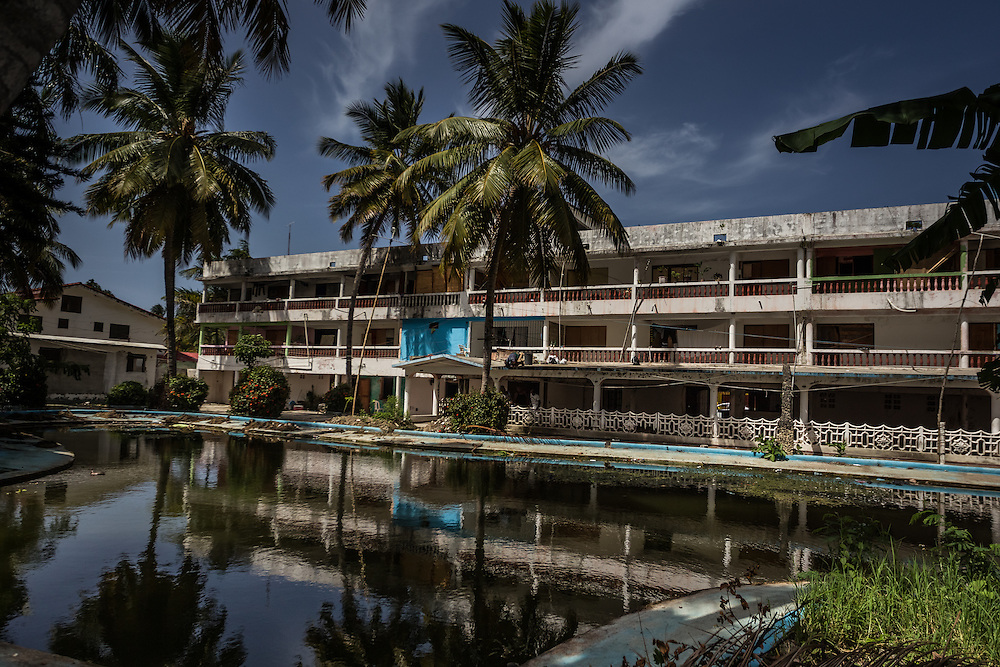 PUERTO PLATA, DOMINICAN REPUBLIC - JUNE 28, 2015: Dozens of Haitian and poor Dominican families live as squatters inside of this abandoned resort that once attracted international tourists in Puerto Plata, on the northern coast of the Dominican Republic.  The resort became a bastion of immigrant life, especially following the 2010 earthquake in neighboring Haiti, with people having taken rooms in the hotel to live, established grocers, and turned former tennis pro shop into a discotheque.  In recent weeks, however, it's been abandoned once again. Haitian residents were scared by the new immigration policy and many fled to other more low profile places or to back to Haiti, in fear of being deported. Their squatter community is symbolic to the changing dynamics of this town and immigration policy. It's sort of the resort that time forgot - twice abandoned and now nearly empty.  PHOTO: Meridith Kohut for The New York Times.