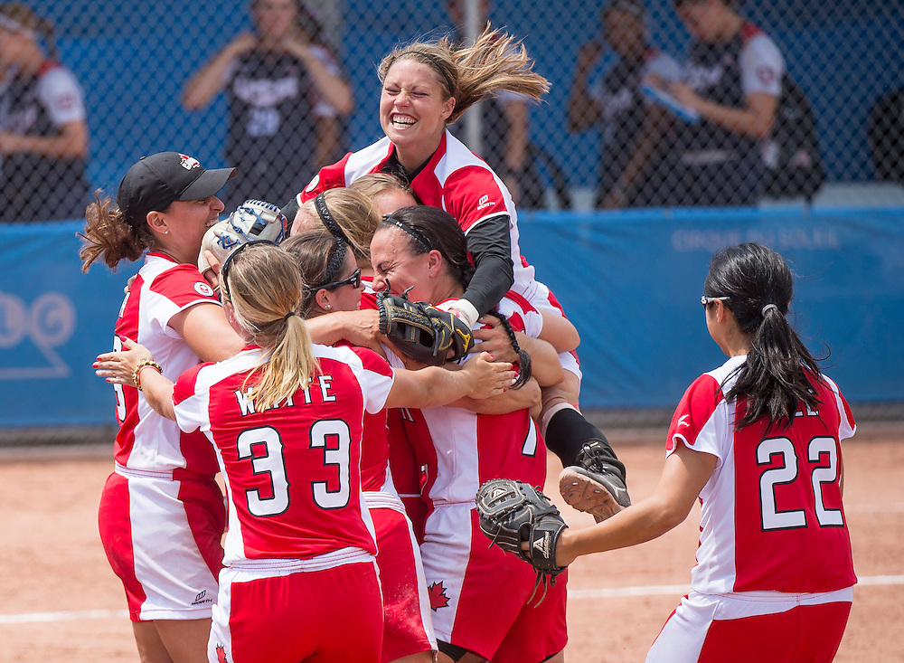 Women's softball finals-USA vs. Canada- Team Canada celebrates their victory against the USA while Valerie Arioto-USA (#20) walks off the field during competition at the 2015 PanAm Games in Toronto.