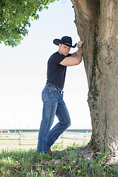 rugged masculine cowboy leaning against a tree
