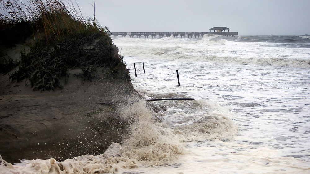 Tropical Storm Irma pounds the sand dunes of the southend beach of Tybee Island, Ga., Monday, Sept., 11, 2017. Tybee officials said wind gusts are reported at 60 miles per hour on the beach.  (AP Photo/Stephen B. Morton)