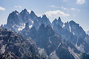 "Sharp peaks of the Cadini Group rise in the Sesto Dolomites, Veneto region, Italy, Europe. In the Cadini di Misurina, Cima Grande rises to 2999 meters (9839 feet), between Cima Piccola and Cima Ovest. The Cadini Group is in the municipality of Auronzo, in the Sesto Dolomites (Dolomiti di Sesto, or Sexten/Sextner/Sextener Dolomiten) which lie north of the Fiume Ansiei valley. From the Rifugio Auronzo toll road, hike for spectacular views around Tre Cime di Lavaredo (Italian for ""Three Peaks of Lavaredo,"" called Drei Zinnen or ""Three Merlons"" in German). The Dolomites are part of the Southern Limestone Alps. UNESCO honored the Dolomites as a natural World Heritage Site in 2009."