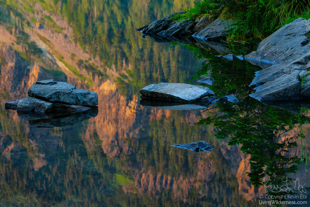 The cliffs surrounding Mowich Lake in Mount Rainier National Park, Washington, cast their golden reflections on the lake's surface in the late evening.
