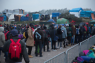 Calais, Pas-de-Calais, France - 24.10.2016    <br />  <br /> Refugees line up to leave the camp. Start of the eviction on the so called &rdquo;Jungle&quot; refugee camp on the outskirts of the French city of Calais. Refugees and migrants leaving the camp to get with buses to asylum facilities in the entire country. Many thousands of migrants and refugees are waiting in some cases for years in the port city in the hope of being able to cross the English Channel to Britain. French authorities announced a week ago that they will evict the camp where currently up to up to 10,000 people live.<br /> <br /> <br /> Fluechtlinge stehen in einer Reihe um das Camp zu verlassen. Beginn der Raeumung des so genannte &rdquo;Jungle&rdquo;-Fluechtlingscamp in der franz&ouml;sischen Hafenstadt Calais. Fluechtlinge und Migranten verlassen das Camp um mit Bussen zu unterschiedlichen Asyleinrichtungen gebracht zu werden. Viele tausend Migranten und Fluechtlinge harren teilweise seit Jahren in der Hafenstadt aus in der Hoffnung den Aermelkanal nach Gro&szlig;britannien ueberqueren zu koennen. Die franzoesischen Behoerden kuendigten vor einigen Wochen an, dass sie das Camp, indem derzeit bis zu bis zu 10.000 Menschen leben raeumen werden. <br /> <br /> Photo: Bjoern Kietzmann