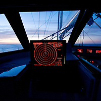 The radar is always on while this large sailing yacht sails towards the dawn of the north Atlantic Ocean. the radar is displayed on a multi purpose waterproof lcd screen that also operate the mechanical systems on the yacht.