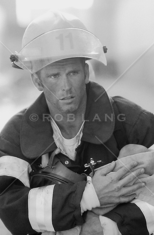 Fireman at work holding a baby