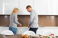 Mid adult couple preparing meal together in kitchen