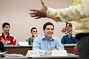 Eric Shainock (left), Ethan Saporito (center rear), and Brien Joyce (center front) listen to professor David Kirch during lecture on stock analysis. Photo by: Ross Brinkerhoff.